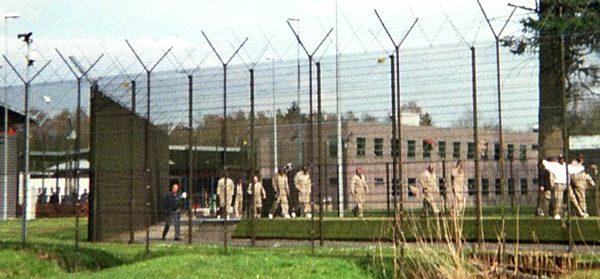 Op de achtergrond verblijfsruimten in een cellenblok.